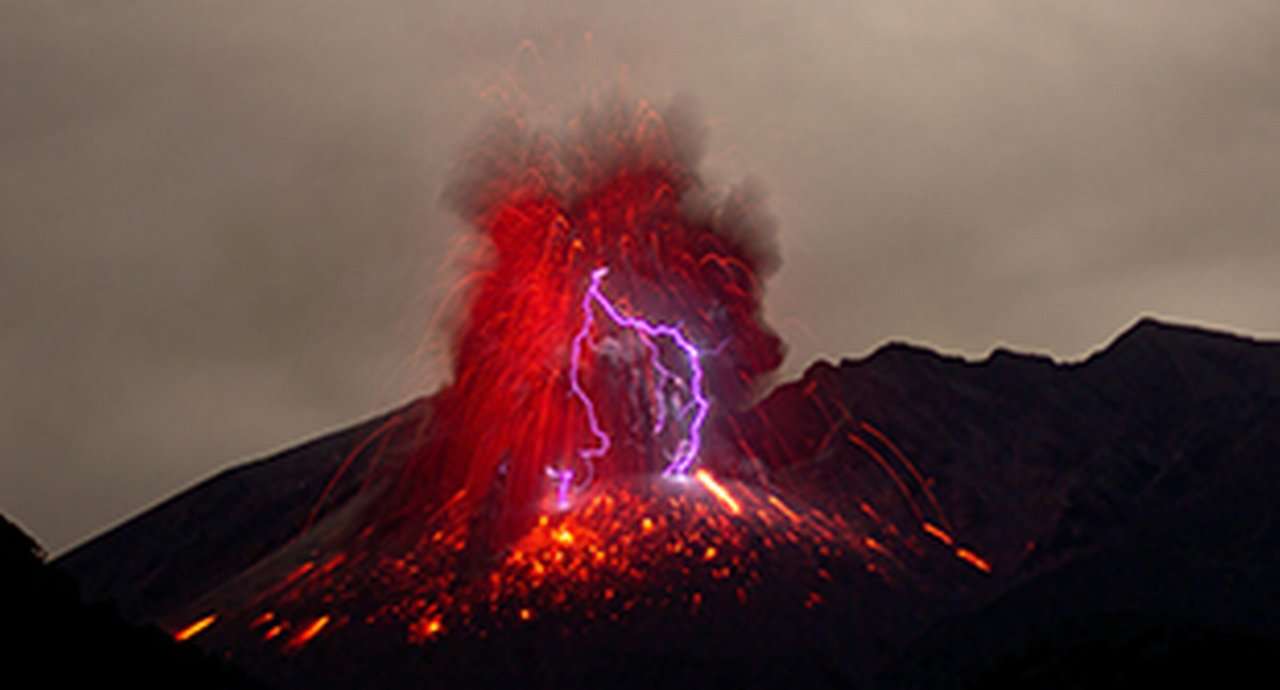 An erupting volcano in vivid red and with magenta lighting