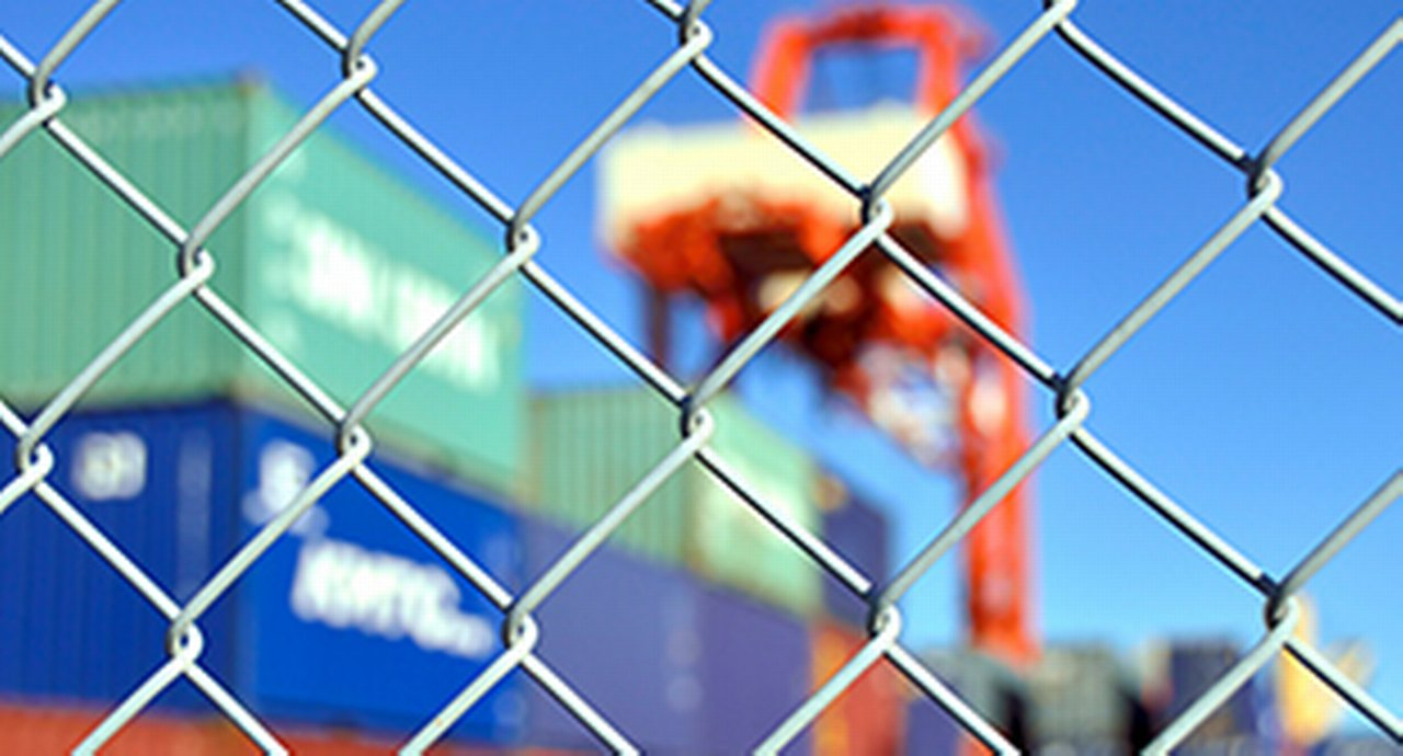 A wire mesh fence in front of a container yard