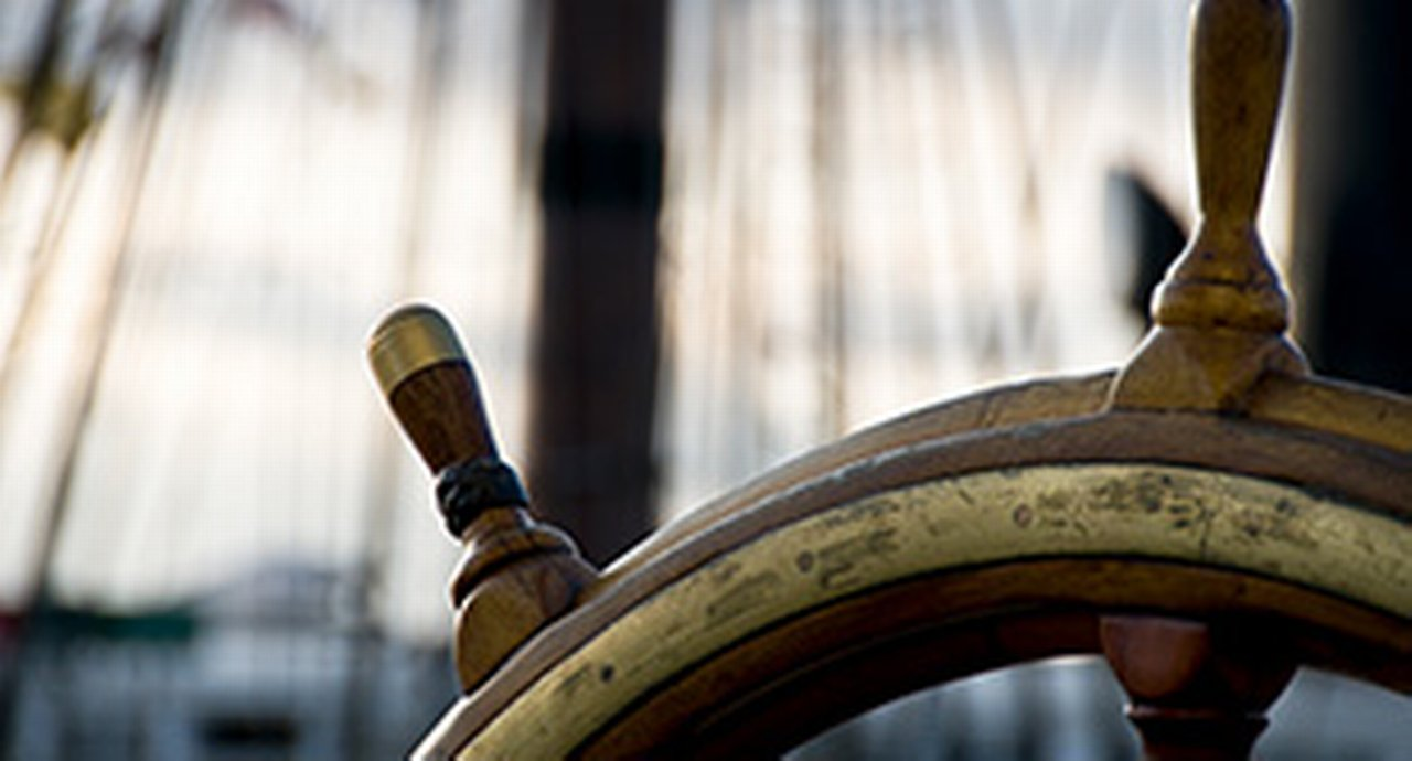 top part of a ship's wheel in front of a blurry boat