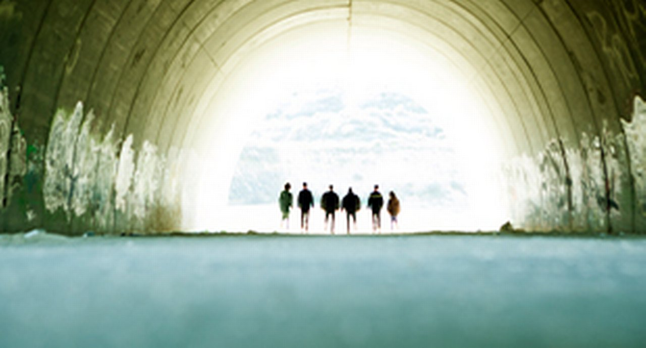 tunnel where 6 people are standing in the light at the end of the tunnel