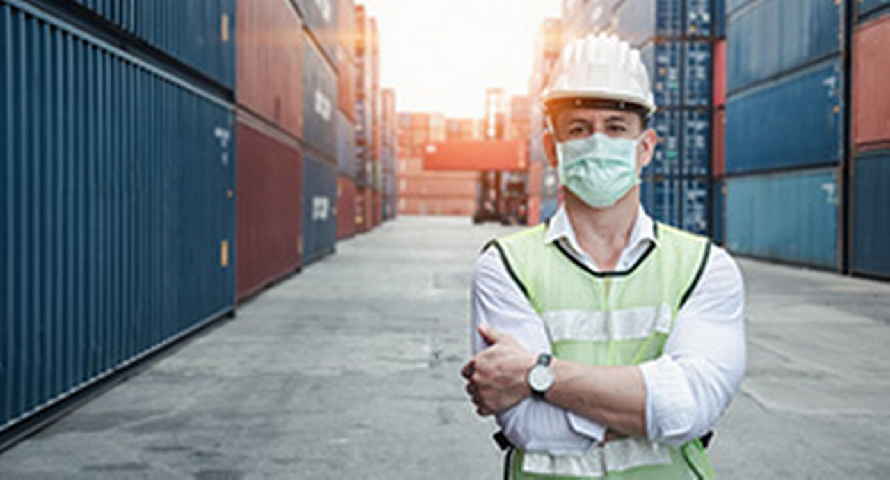 A masked worker in a container port
