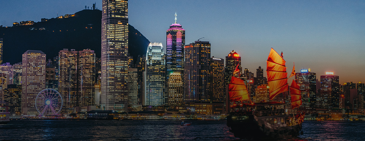 Victoria Harbour at night with brightly illuminated skyscrapers in the background