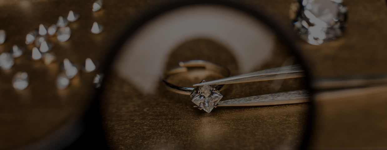 A diamond in tweezers viewed through a magnifying glass